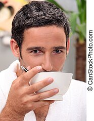 Man having cup of coffee at home