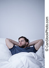 Man having difficulty falling asleep - Photo of young man...