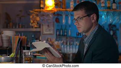 Man having drink and working with pad in the bar