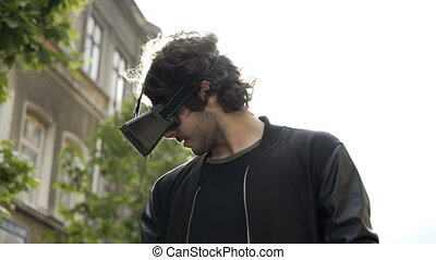Man having fun with virtual reality glasses outdoor in the city surprised by new vr experience