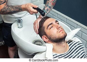 Man having hair dress - Young man having his hair washed in...
