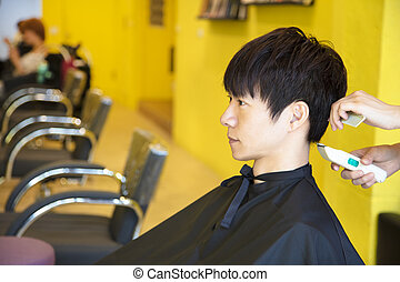 Man having haircut with hair clippers