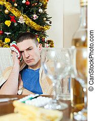 Man having hangover during holidays at home - Man having...