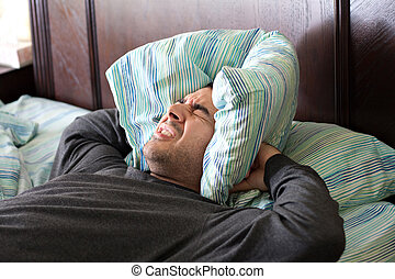 A man having trouble sleeping squeezes a pillow around his ears for some peace and quiet.