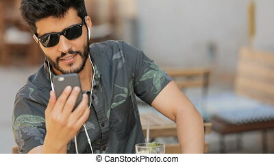 Man Having Video Call in Street - Handsome black-haired man...