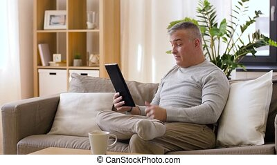 man having video chat on tablet pc at home - technology,...