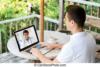 man having video chat with doctor on laptop