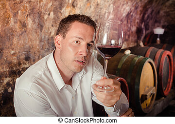 man having wine tasting in cellar