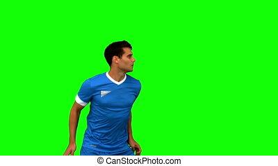 Man heading a football on green scr