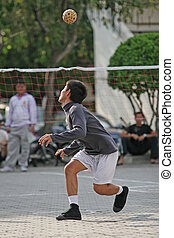 Man heads the ball in a game of Sepak Takraw