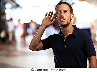man hearing sounds at shopping center