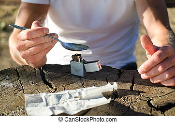 Man heating crack cocaine in a spoon - Man seated at a ...