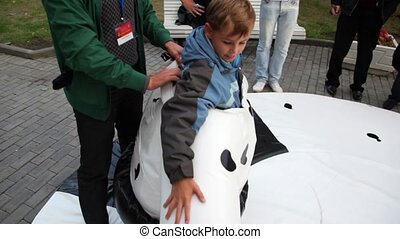 Man help boy to put on cow suit, people stand around
