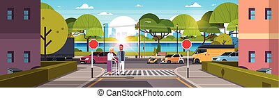 man help senior woman with walking stisk crossing street urban city traffic cars on road crosswalk river green trees wooden benches cityscape background horizontal flat
