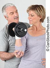 Man helping a woman lift a dumbbell