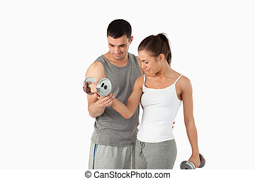 Man helping a woman to work out
