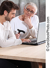 Man helping an elderly lady with her laptop