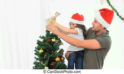 Man helping his daughter to decorate the Christmas tree