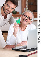 Man helping his mother keep a digital record of her healthcare expenses