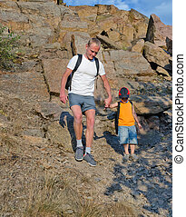 Man helping his son to hike on a rough area