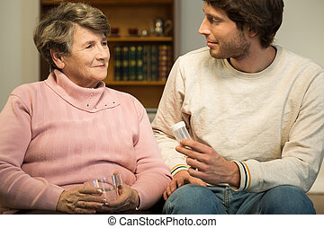 Man helping ill eledrly woman