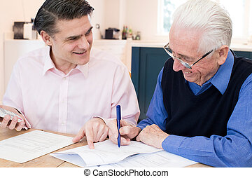 Man Helping Senior Neighbor With Paperwork