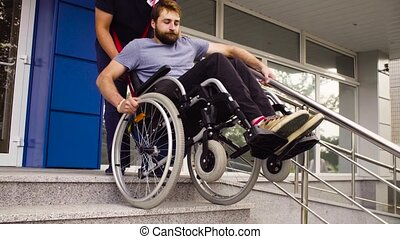 Man helping to move down to a disabled man