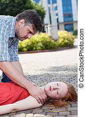 Man helping unconscious woman on the street