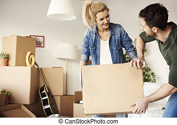 Man helping woman carrying the cardboard box