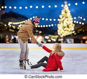 man helping woman on christmas skating rink - holidays and...