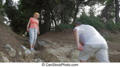 Man helping woman to make the way in woods