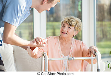 Man helps to stand up an older woman at nursing home