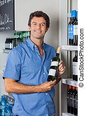 man, het tonen, wijn fles, in, supermarkt