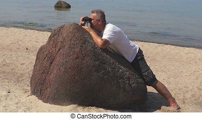 Man hides behind the stone and using binoculars