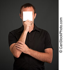 Man hiding behind a blank note
