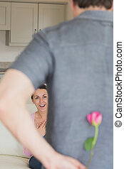 Man hiding flower behind his back for wife