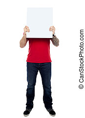 Man hiding his face behind blank white ad board
