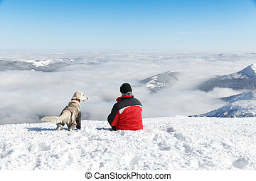 Hiker and his dog, Golden retriever, watching the beautiful mountain landscape. Beautiful inspirational landscape, trekking and activity