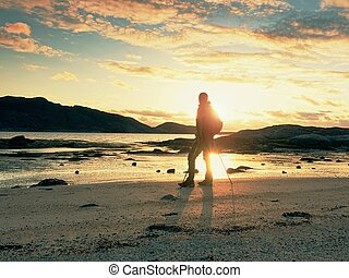 Man hiker backpacker walking with backpack on sea shore at sunny evening. Adventure, tourism active lifestyle.