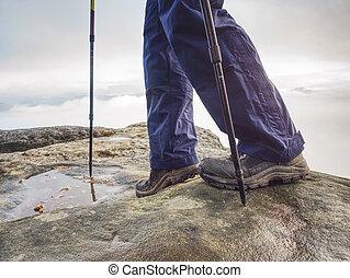man hiker legs stand on mountain peak rock