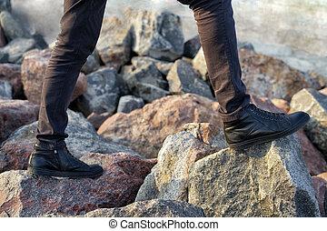 man hiker legs standing on mountain stone peak rock