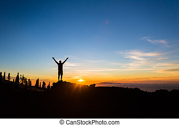 Man hiker silhouette with arms outstretched enjoy mountains...