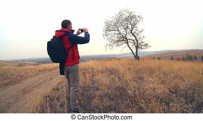 man hiker traveler with a backpack in the autumn is on the way to nature is a solitary tree travel