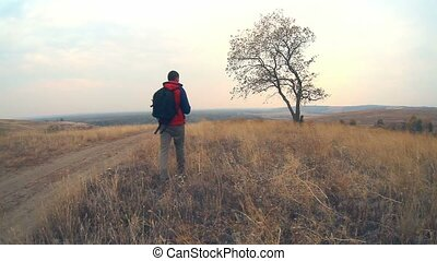 man hiker traveler with backpack in autumn is on the way to nature is solitary tree travel
