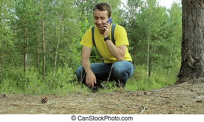 Man hiker walking through the forest and talking on the phone. Yellow T-shirt and jeans with suspenders. Technology in the wild
