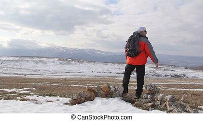 Man hiker walking through the snowy mountain plateau