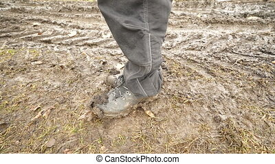 Man hiker wearing a pair of muddy hiking boots on dirt track