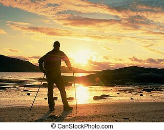 Man hiker with a backpack and trekking pole standing at rocky shore and looking on the evening horizon