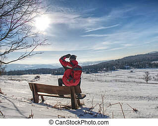 Man hiker with backpack in winter time walk