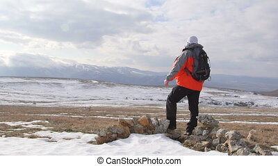 Man hiker with outstretched arms on snowy mountain plateau -...